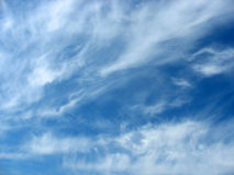 Blue sky background with wavy fleecy clouds royalty free stock photography