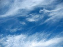 Blue sky background with wavy fleecy clouds Stock Images