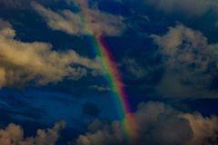 Blue sky, clouds and rainbow all of a sudden. stock photos