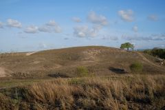 Blue sky, beautiful clouds, above the savanna of Lolomogho hill, southwest Sumba border with West Sumb stock photos