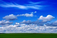 Blue sky with beautiful clouds and green field Royalty Free Stock Photos
