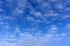 The blue sky begins to tighten with rain clouds stock image