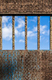 Blue sky behind bars. Of a rusty iron door Royalty Free Stock Photo