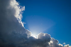 Blue sky behind dark clouds. Sun and blue sky behind dark clouds Royalty Free Stock Photography