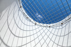 Blue sky behind round window with metal grid Stock Image
