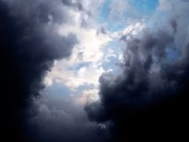 Blue sky behind stormy clouds. Light clouds and blue sky behind dark storm clouds Royalty Free Stock Image