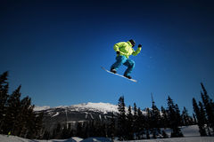 Blue Sky, Big Air. A snowboarder takes flight on Whistler Mountain Stock Photo
