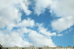 Blue sky with big clouds and the roof of the house.  royalty free stock photos