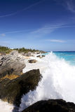 Blue sky, big waves. Waves crashing in the foreground of a beautiful tropical coastline royalty free stock image