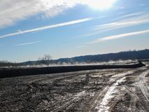 Blue sky Black Dirt Steam rising on sunny morning royalty free stock photography