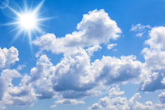 Blue sky bright sun. A blue sky with bright sun and clouds royalty free stock image