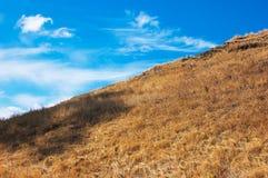 Blue sky, brown slope Stock Image