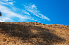 Blue sky, brown slope Stock Photo