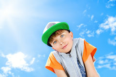 Blue sky. Cheerful smiling boy looking at the camera against the blue sky. Summer Stock Photo