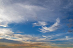 Blue sky with Cirrus Clouds formation and yellow shade of sunset Royalty Free Stock Images
