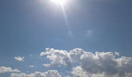 Blue sky with clear clouds and sun rays royalty free stock photo