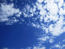 Blue sky. Clear blue sky with fluffy clouds Royalty Free Stock Image