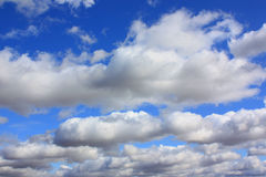 Blue sky with clouds. A blue sky background with big fluffy white clouds Stock Photography