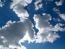 Blue sky and clouds. Natural background with blue sky and sun  through the white clouds Stock Photography