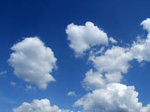 Blue sky with clouds. Dark and bright blue sky with white clouds Royalty Free Stock Image