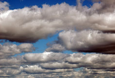 Blue sky with clouds. Dark and bright blue sky with white clouds Stock Images