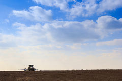 Blue sky clouds above dark ploughed field seeder in spring. Blue sky with cumulus clouds above dark ploughed field and seeding machine in spring Stock Photography