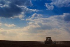 Blue sky clouds above dark ploughed field with tractor. Fantastic blue sky with cumulus clouds above dark ploughed field and tractor in spring Stock Image
