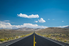 Blue sky and clouds above desert highway Stock Images