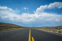 Blue sky and clouds above desert highway. Dark clouds threatening a rain storm above desert highway Stock Image