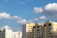 Blue sky and clouds above tall buildings. With copy space stock photography