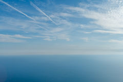 Blue sky with clouds and airplane trails over the Black sea. Nature composition. Royalty Free Stock Photo