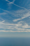 Blue sky with clouds and airplane trails over the Black sea. Nature composition. Royalty Free Stock Photos