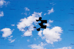 Blue sky with clouds as a puzzle. (with a black hole instead of one piece royalty free stock photography