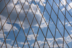 Blue sky with clouds behind metal lattice. Royalty Free Stock Images
