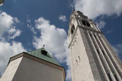 Blue sky with clouds behind white belfry church of Cortina d`Ampezzo, Veneto, Italy. stock image