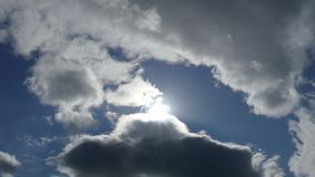Blue sky and clouds covering sunshine - 4K Stock Image