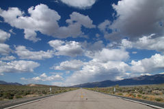 Blue sky with clouds in the desert and a road Royalty Free Stock Photo