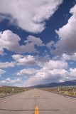 Blue sky with clouds in the desert and a road Stock Photography