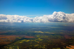 Blue sky,clouds and earth visible through them from a plane window Royalty Free Stock Photography