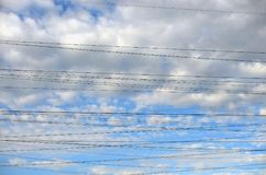 Blue sky, clouds and electric wires. Stock Photography