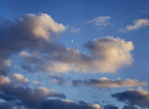 Blue sky with clouds, evening, moon. A blue sky with clouds, evening, moon Stock Image