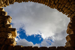 Blue sky with clouds framed by ancient arc of bricks, copy space. Blue sky with clouds background framed by ancient arc of bricks and blocks, copy space for any Stock Photo