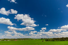 Blue sky, clouds and green meadow Stock Photos