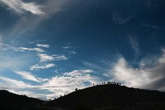 Blue sky with clouds hill mountains with contours of people royalty free stock photos