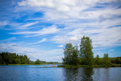 Blue sky with clouds and the island in the lake Royalty Free Stock Images