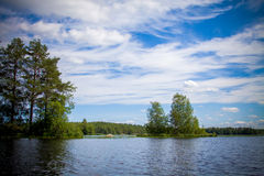 Blue sky with clouds and the island in the lake Royalty Free Stock Photo