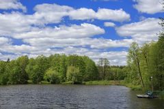 Blue sky with clouds, lake and forest Royalty Free Stock Image