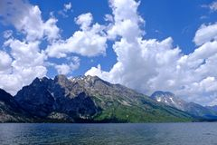 Blue sky with clouds and mountains by lake. royalty free stock image