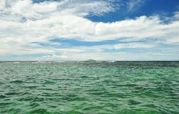 Blue sky with clouds and ocean. Blue sky with clouds and green ocean Royalty Free Stock Image