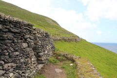 A large dry stone wall in Dingle Peninsula in Ireland in the summer. Blue sky with clouds and an old dry stone wall of bricks at the countryside along the ocean royalty free stock photography